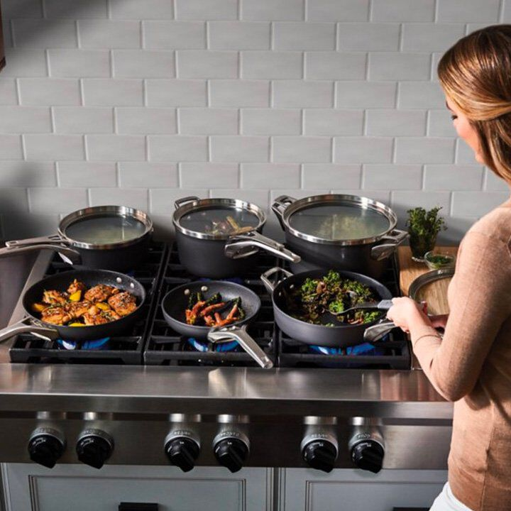 women preparing food on stove with assorted nonstick cookware